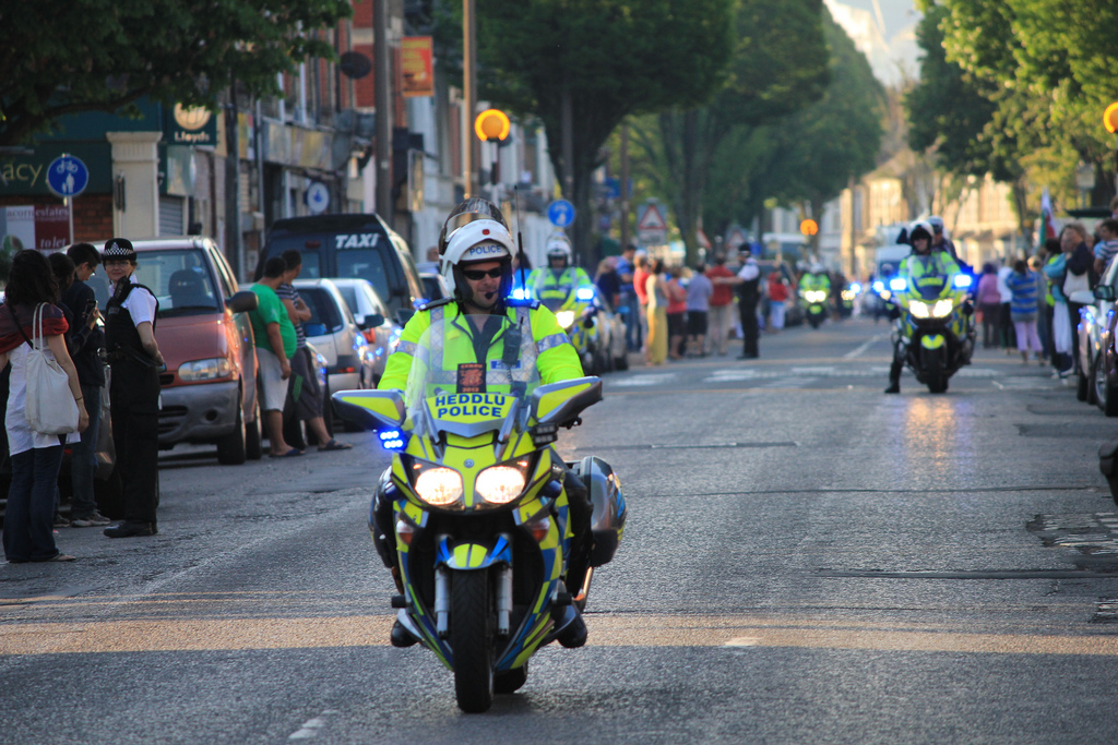 A police officer on a motorcycle in high-yis yellow reflective gear controls traffic in a public street