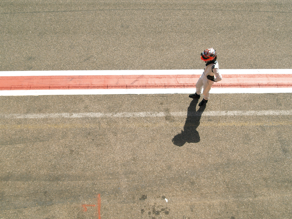 A racing driver, hands on hips, shown alone in the pit lane waiting for his chance to race
