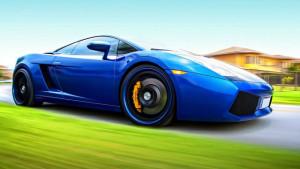A metallic Blu Caelum Lamborghini Gallardo coupe being photographed in motion from the side profile
