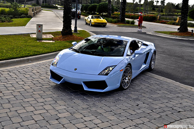A 2009-Lamborghini-Gallardo-LP560-4-Celeste-Cepheus (light-blue) pulling up on a cobbled, nicely paved driveway