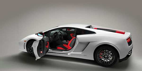 Profile view press photo of a 2012 Lamborghini Gallardo LP560-4 Bianco Rosso with the driver's side door open, showing the black/red themed interior