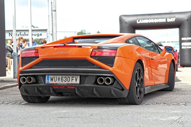 A rear 3/4 shot of a 2013+ Gallardo LP560-4 Nuova in Arancio Borealis at a Lamborghini gathering in Europe