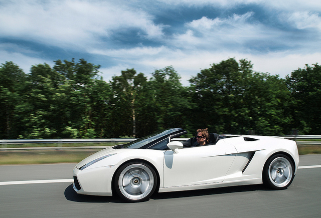 Gallardo Spyder in white with top down cruising, rolling profile shot