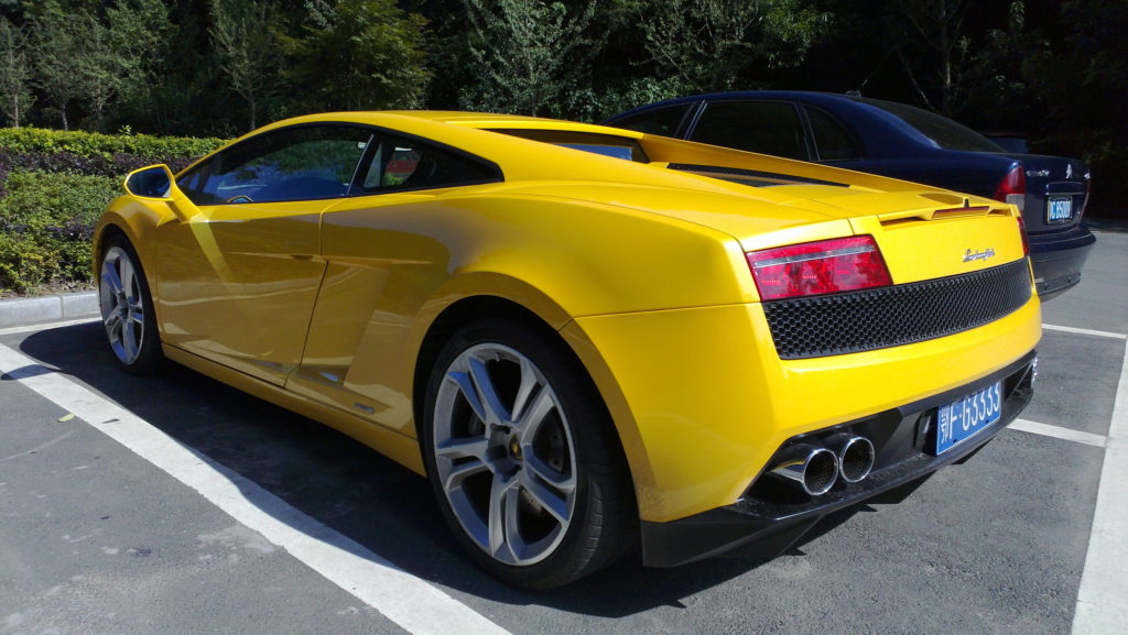 A rear 3/4 of a yellow Lamborghini-Gallardo-LP550-2 parked outside with some bushes and trees in the background
