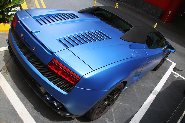 Elevated rear 3/4 shot of a Lamborghini-Gallardo-LP560-4-Spyder in matte blue with its black top up