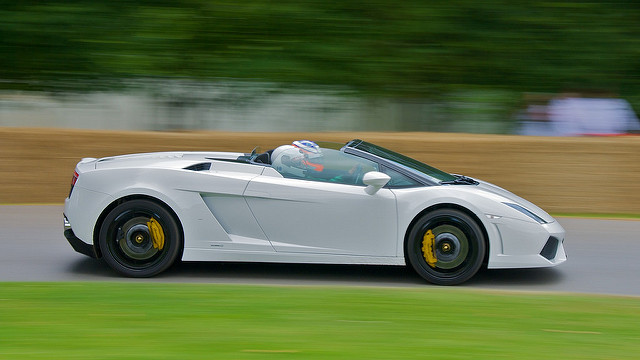 A white Lamborghini-Gallardo-LP560-4-Spyder being demonstrated with the top down at a speed festival