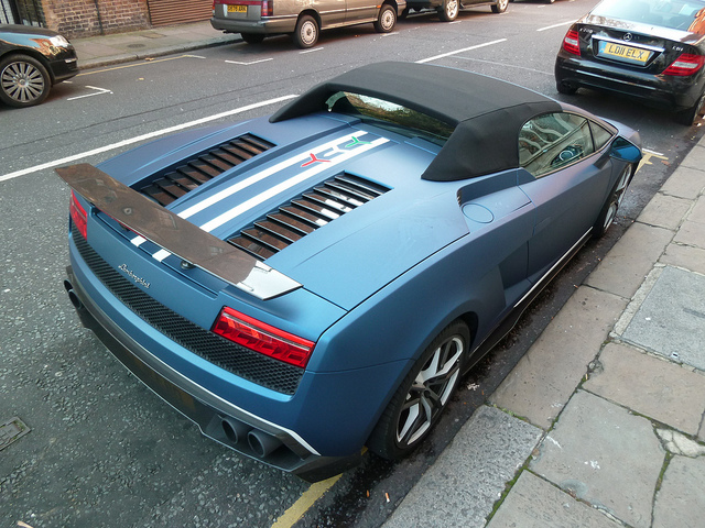 "A photo of a matte blue Lamborghini-Gallardo-LP570-4-Spyder-Performante showing the unique dual white stripe and Italian tricolor ""Y"" on the engine cover"