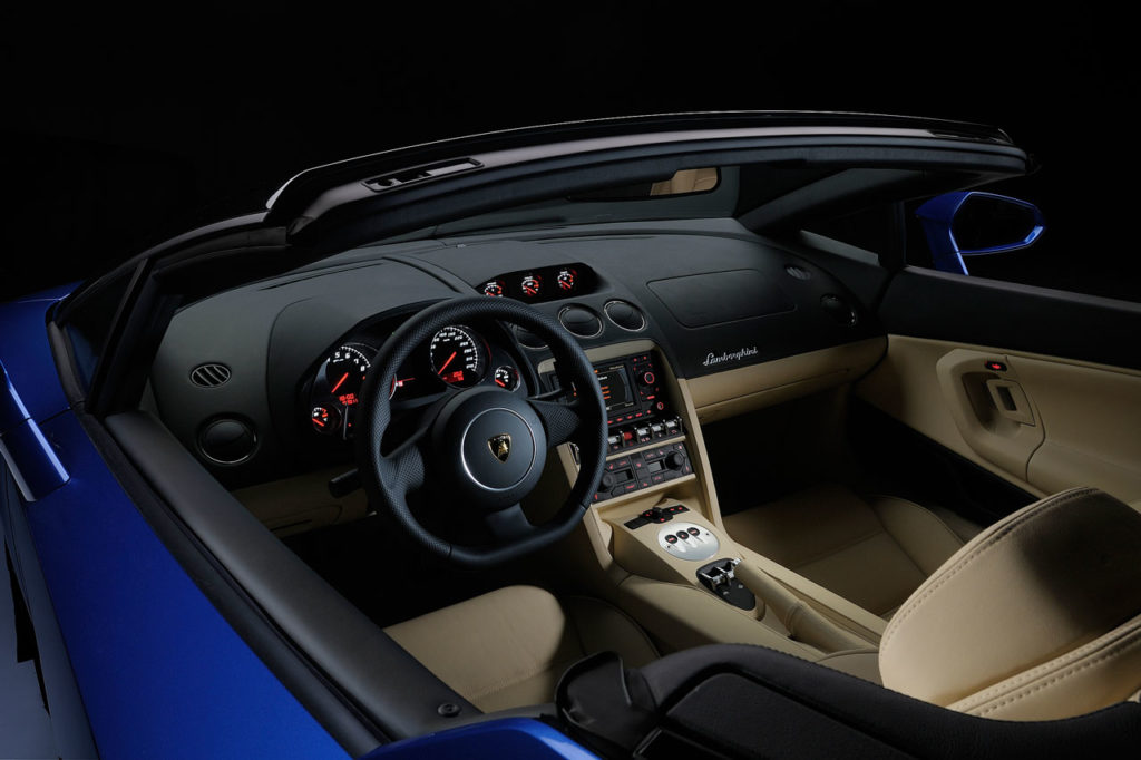 A photo looking down into a lamborghini-gallardo-lp550-2-spyder with the top open showing a black and tan leather color combo