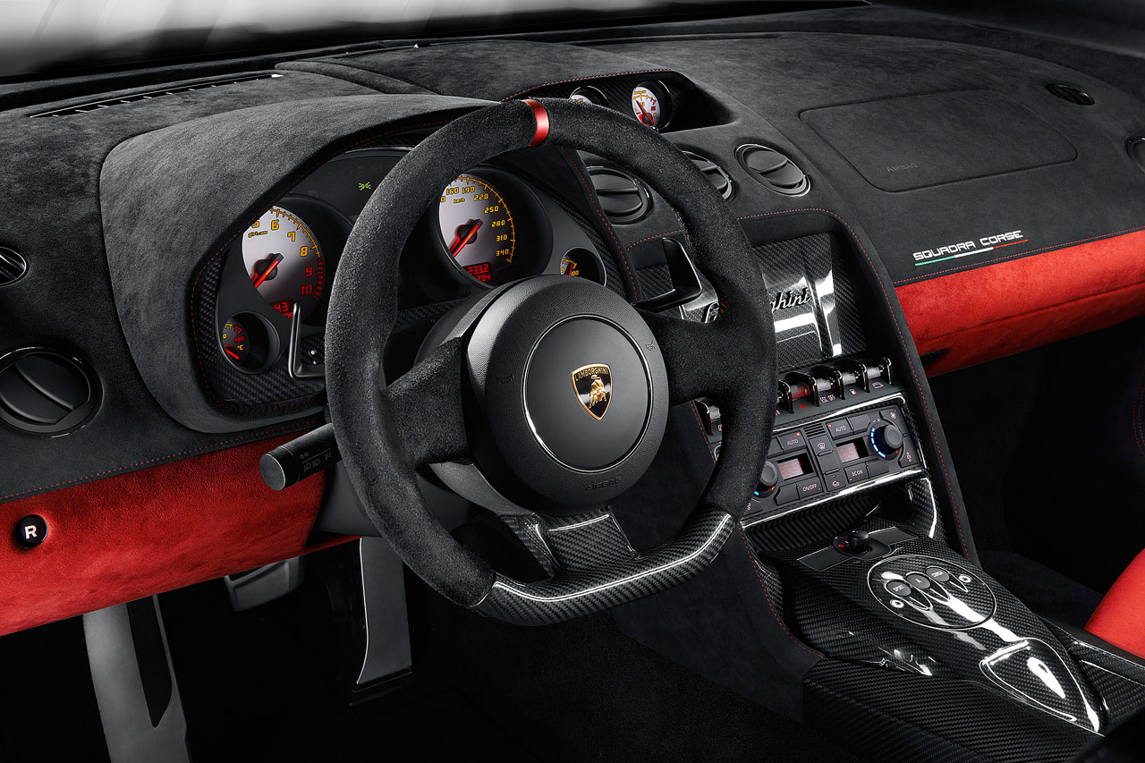 An interior shot of a 2014 Lamborghini Gallardo LP570-4 Squadra Corse showing the two-tone black/red alcantara theme matched with carbon fiber for the center tunnel, bottom of the steering wheel and Squadra Corse logo on the glovebox