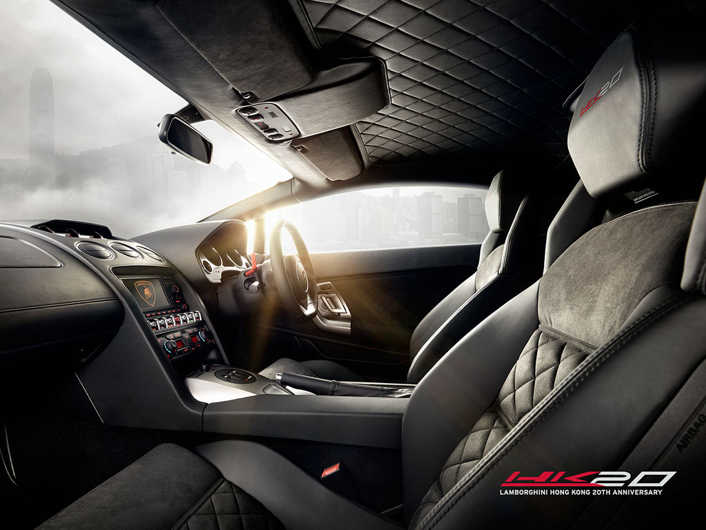 An photo of the interior of a Lamborghini-Gallardo-LP550-Hong-Kong-HK20-Edition showing the black leather and black alcantara configuration, HK20 logos on the headrests and the red e.gear paddles