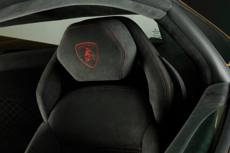 A detail shot of a Lamborghini-Gallardo-LP560-4-Gold-Edition's black alcantara seat, highlighting the headrest with red stitching and a red Lamborghini logo