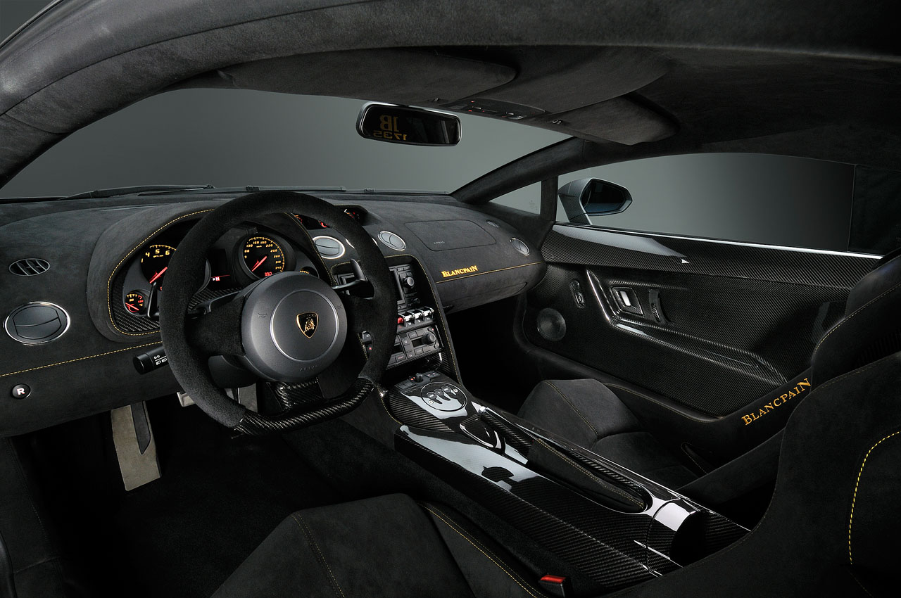 An photo of the interior of a lamborghini-gallardo-lp570-4-blancpain edition from the driver's vantage point showing the extensive use of alcantara and carbon fiber throughout the cabin