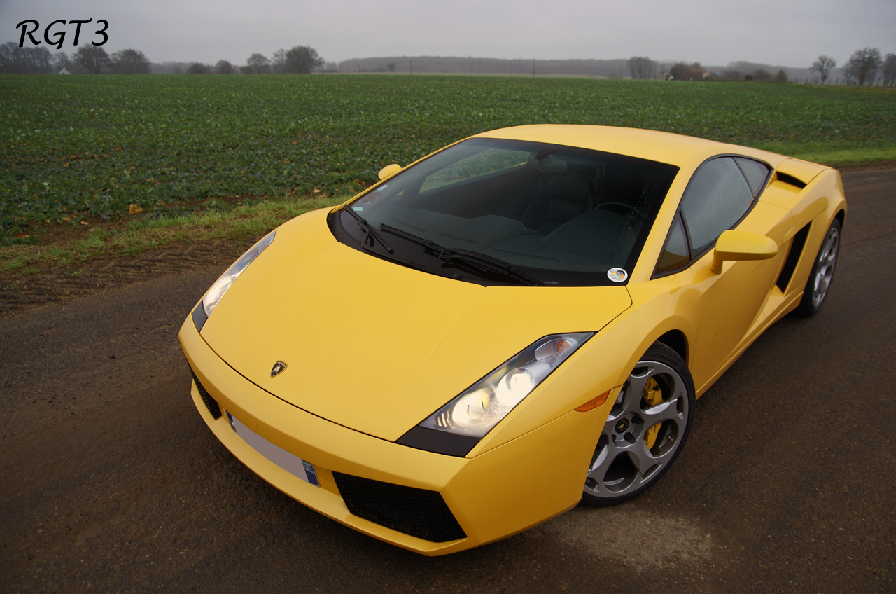 A 2004-2005 Lamborghini Gallardo in yellow shot in a slightly elevated 3/4 front profile with its HID headlights on, in front of a large agricultural-looking field