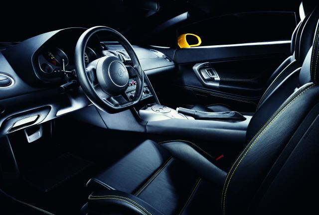 An interior photo of a 2004 Lamborghini Gallardo photographed from the driver's side door showing a black leather interior with yellow contrasting stitching, e.gear shifter paddles